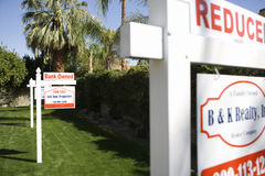 Real Estate Signs at Foreclosed Property. Closeup of real estate signs at foreclosed property Stock Photo