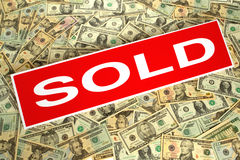 Real Estate Sold Sign over Dollar Money Background. Real estate red sold rider sign over dollar bills money background royalty free stock photography