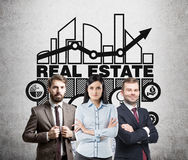 Real estate team, concrete wall. Business team members are standing with crossed arms near a blackboard with a real estate graph and a sketch drawn on it Royalty Free Stock Photos