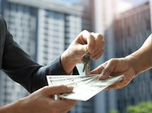 Real estate trading,Hand people are paying the dollar with other. Hand holds the keys,background is a blurred condominium image Royalty Free Stock Photos