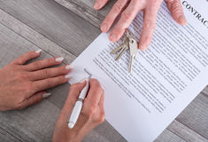 Real estate transaction. Estate agent presenting house keys and contract to customer Stock Image