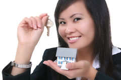 Real Estate Woman. A real estate woman holding a key and house Stock Photo