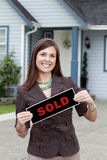 Real estate woman holding a sold sign. A young female real estate agent holds a sold sign outside a house royalty free stock photography