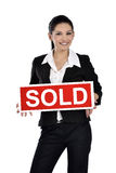 Real estate woman holding a sold sign Stock Photo
