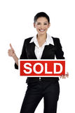 Real estate woman holding a sold sign. Young successful mixed race caucasian real estate agent or owner holding a sold sign for a sold house. Isolated on white stock image