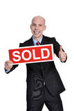 Real estate man holding a sold sign Stock Photos