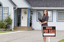 Real estate woman standing outside a house for sale Royalty Free Stock Image