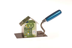 Real estates. House constructions costs through money on a workers trowel royalty free stock images