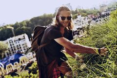 Real explorer. Handsome young man in casual clothing looking at camera and smiling while standing on the hill with buildings in the background Stock Photography