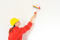 Real female painter painting wall Royalty Free Stock Photos