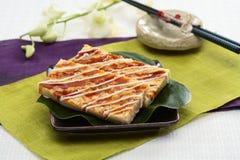 Real firmer okonomiyaki on green leaf and black plate in Japanes Stock Photo