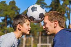 We are the real football team. Happy father and son are holding ball on their heads together. They are looking at each other and smiling Stock Images