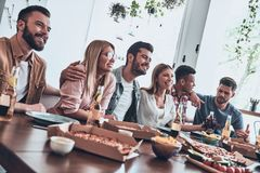 Real friendship. Group of young people in casual wear communicating and smiling while having a dinner party stock photography