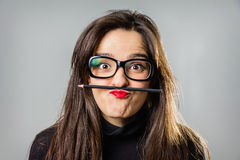 Real girl holding a pencil with her red lips Stock Photos