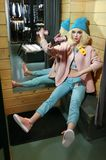 Real girl looks like a barbie doll in shop on sale. Girl dressed in pastel blue and pink colors. Clothes stock images