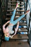 Real girl looks like a barbie doll in shop is on sale. Girl fals from stairs dressed in pastel blue and pink colors. Clothes royalty free stock images