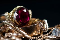Real gold jewelry  with gems close up macro. Shot isolated on dark background Royalty Free Stock Photo