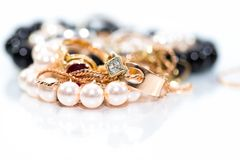 Real gold jewlery, diamonds, gems, rings, neckless with pearls close up shot. White background, on shiny surface royalty free stock image
