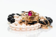 Real gold jewlery, diamonds, gems, rings, neckless with pearls close up shot. White background, on shiny surface stock photo