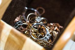 Real gold rings with diamonds, gems, chains. In hand carved wood jewelry box stock photos