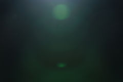 Real green lens flare over dark background stock image