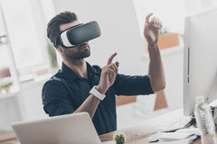 It is so real!. Handsome young man in VR headset gesturing and smiling while sitting in creative office Stock Photos