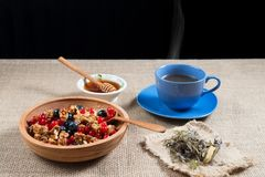 Real herbal tea in a blue Cup filled on a napkin, and honey in a bowl of honeycomb in a wooden bowl with red currants and blueber Royalty Free Stock Photos