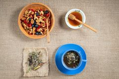 Real herbal tea in a blue Cup filled on a napkin, and honey in a bowl of honeycomb in a wooden bowl with red currants and blueber Stock Photo