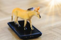 Real horse model toy in action of running on surface of device. stock photos