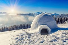 Real igloo and sun. Real snow igloo in the mountains under blue sky and sun Stock Image