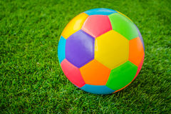 Real leather Colorful multi colour Soccer ball on green grass . Stock Photo