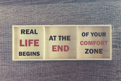 Real life begins at the end of your comfort zone. Inspirational quote. Written on wooden box royalty free stock photos