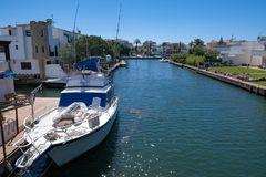 Real Life in resort city with marine canal and boats. Beautiful view on marine canal with moored boats and classic white houses in Spain. Resort town landscape royalty free stock images