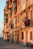 Real life on Valletta street during orange sunset - nobody on sidewalk. And clothes drying on typical maltese balcony Stock Photo
