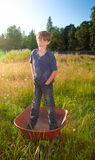 A real life young boy standing in a wheelbarrow. A real life young boy, with a faded shirt and dirty jeans, standing in a wheelbarrow in rural landscape Stock Photos
