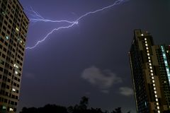 The Real Lightning Flashing in Night Sky over High Buildings of Bangkok. Thailand Stock Photos