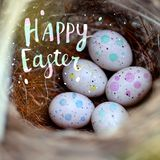Real little eggs in a straw nest. The concept of Easter. Inscription Happy Easter. Selective focus. stock images
