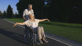 Real love of senior couple with paralyzed wife in park stock footage