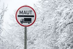 Real Maut sign for lorrys in the snow stock photo