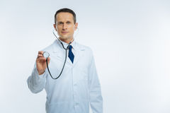 Real medical professional with stethoscope listening to patient heart Stock Photo