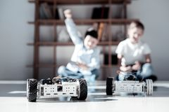 Overjoyed kids racing while playing with robotic vehicles. Real men activity. Selective focus on robotic toys driven by extremely excited friends sitting on the Royalty Free Stock Image
