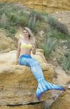 A mermaid sits on a rock royalty free stock images