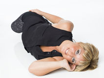 Real middle aged woman laying on white floor Stock Images
