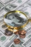 Real money. One hundred dollar banknotes, different value coins and golden magnifier royalty free stock images