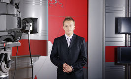 Real News presenter and television camera. Blond middle age news presenter in studio in front of the camera in live transmission Stock Image