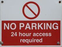 NO PARKING 24 hour access required. A real no parking sign done in bright red so you cannot miss it Stock Image