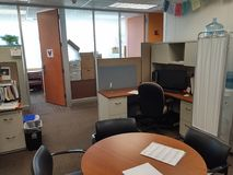 Real office space with desks and office doors open. Papers sun thru windows glass wall chairs stock images