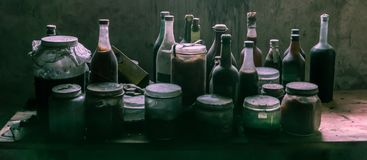 Dusty old glass bottles and cans with suspicious content stock photos