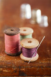 Real old reels spoon treads with needle and thimble on old woode. N table Royalty Free Stock Photo