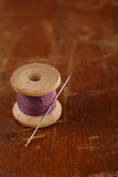 Real old reels spoon treads with needle and thimble on old woode. N table Stock Photo